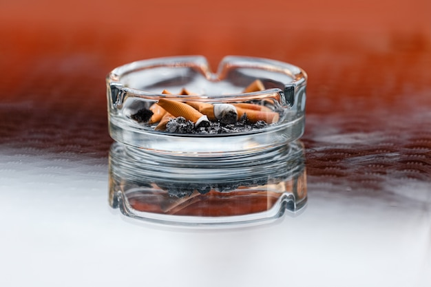 A dirty ashtray with cigarette ash and butts