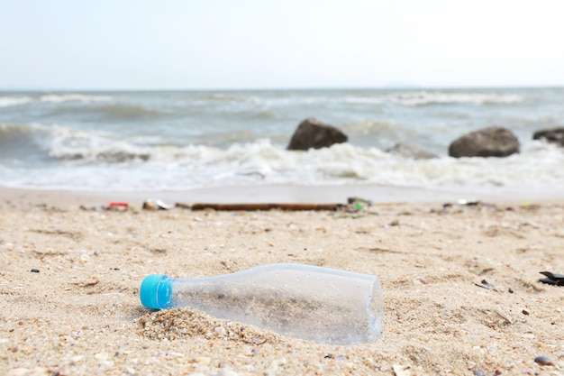 Грязный пляж заполнен пластиковыми загрязнениями, мусором и отходами на песчаном