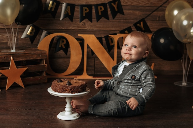 A dirty birthday boy in a gray suit eats a chocolate cake on a brown background
