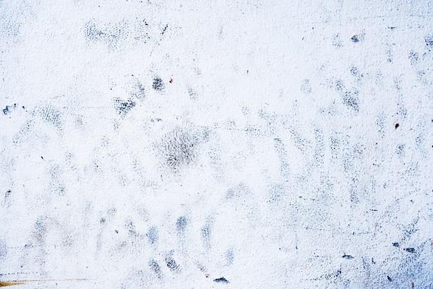 白いセメントの壁のテクスチャに汚れた黒塗られた汚れ