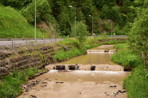Dirty brown water stream in a river with small waterfalls near the road due to flooding