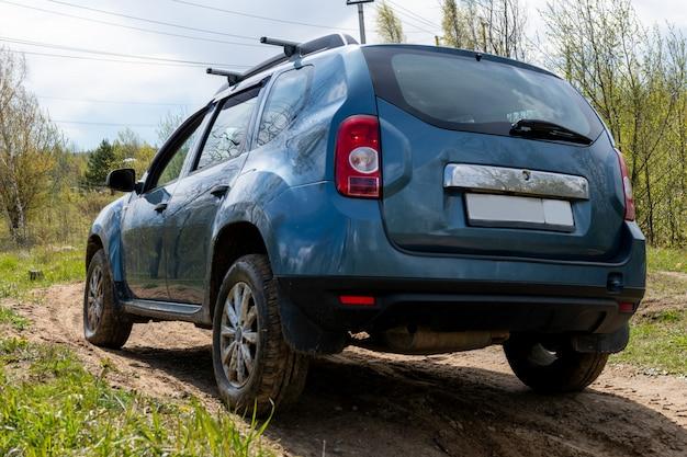 Грязный автомобиль на грязной дороге вид сзади.