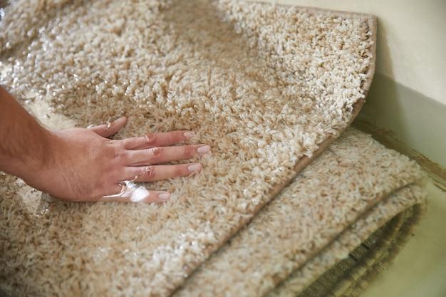 Замачивание грязных ковров в специальном химическом растворе при чистке ковров
