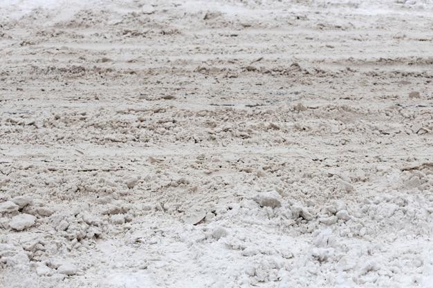 冬の汚い街。道路上の雪の山。高品質の写真