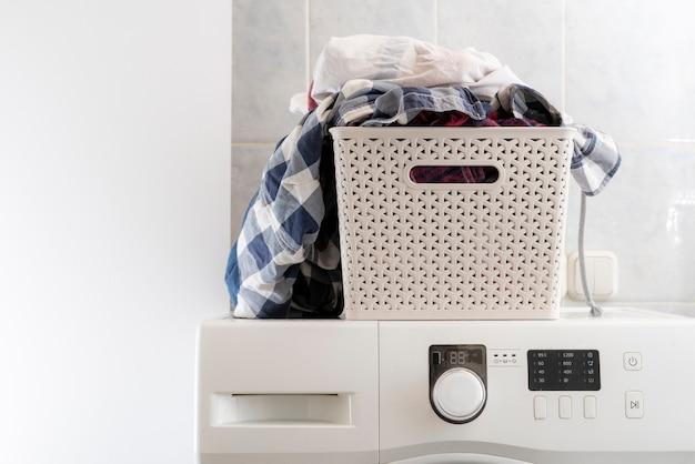 洗濯物のプラスチックバスケットの汚れた服は、洗濯機とテーブルに横たわっていたb