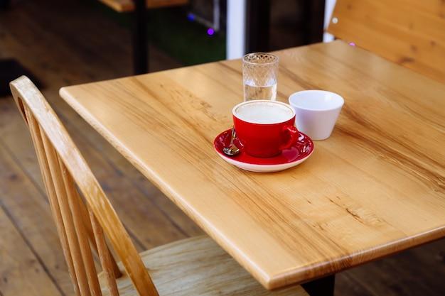 汚れたコーヒーカップ、カプチーノ、コップ一杯の水が木製のテーブルの上に立っています。コーヒーブレイク。味と香りをお楽しみください。