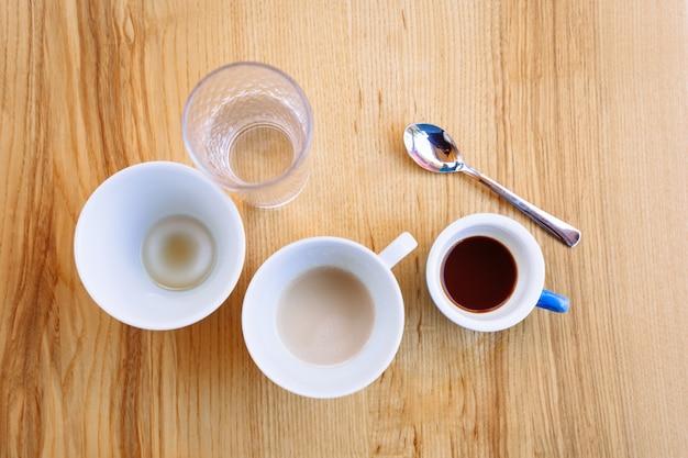汚れたコーヒーカップカプチーノとコップ一杯の水が木製のテーブルの上に立つコーヒーブレイクフラットレイ