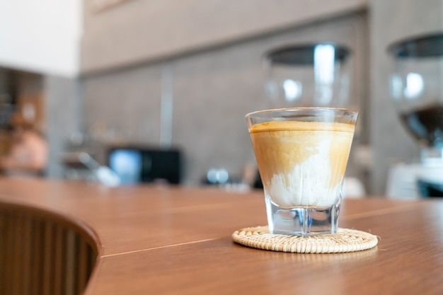 Dirty coffee glass (cold milk topped with hot espresso coffee shot) in coffee shop