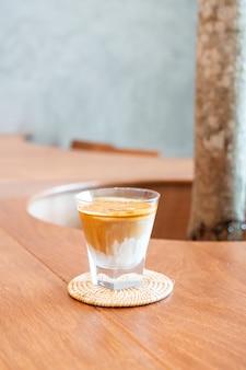 コーヒーショップの汚れたコーヒーグラス(冷たいミルクに熱いエスプレッソコーヒーショットをトッピング)