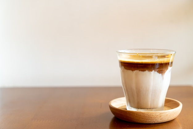 Dirty coffee - a glass of espresso shot mixed with cold fresh milk in coffee shop cafe and restaurant Premium Photo