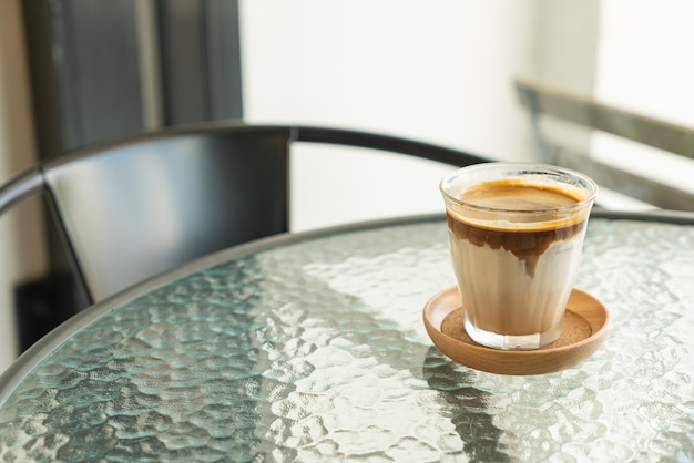 Dirty coffee - a glass of espresso shot mixed with cold fresh milk in coffee shop cafe and restaurant
