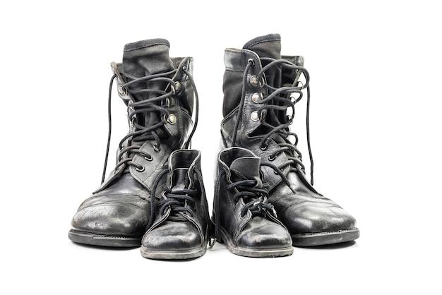 大人と子供のクリッピングパスを白で隔離される汚れた戦闘ブーツ