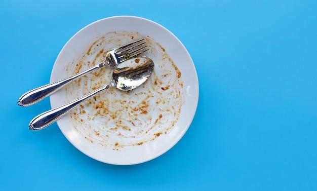 青の背景に汚れた皿。上面図