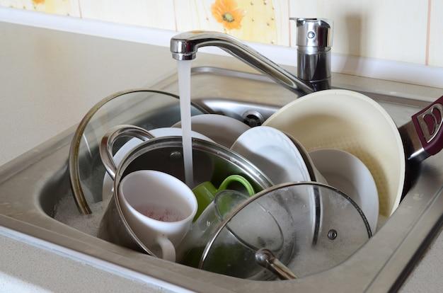 Грязная посуда и немытая кухонная техника лежат в пенной воде под краном из кухонного крана.