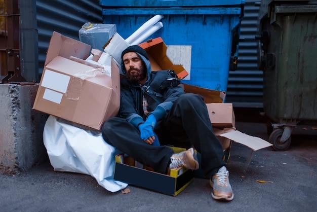 汚い酔った乞食は、街の通りのゴミ箱のゴミの中にあります。