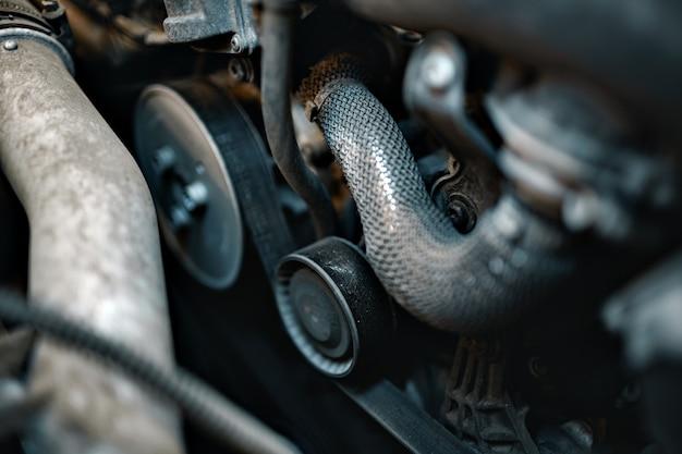 자동차 후드 아래 더러운 엔진을 닫습니다.