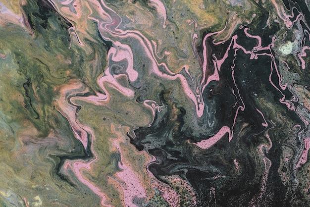 진한 녹색, 주황색 및 분홍색 색조와 검은 얼룩이있는 더러운 유체 예술 배경. 아크릴 페인트의 섬뜩한 효과. 늪지 색조의 액체 잉크. 믹스 마쉬 색상으로 독성 초현실적 인 추상 질감입니다.