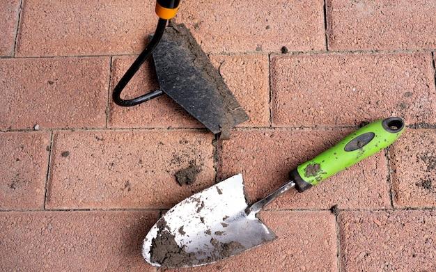 Грязные садовые рабочие инструменты лопаты запачканы в земле в винтажном, старые ретро садовые инструменты над коричневой почвой заделывают, вертикально. сельское хозяйство, садоводство, обработка почвы, концепция деревенской жизни.