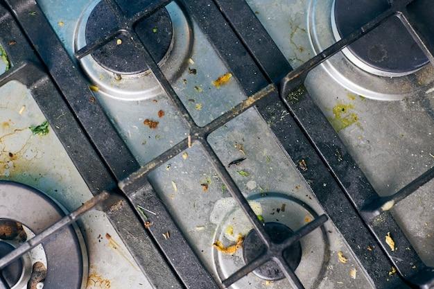 음식이 남은 더러운 가스 스토브 상단. 기름기가 많은 더러운 강철 주방 쿡탑. 봄철 청소, 주방의 오래된 지방 얼룩, 튀김 반점, 기름 튀김 및 탄 조각 제거