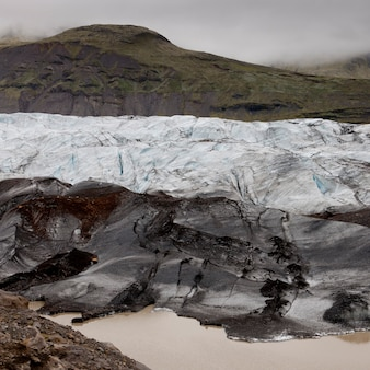 Dirty glacier melting into lake at shoreline, below misty mountain valley