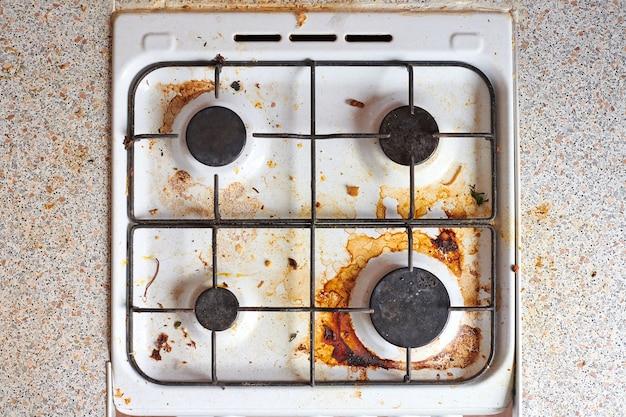 食べ物の残り物が入った汚れたグリースストーブ。脂っこい斑点、古い脂肪の汚れ、揚げ物の斑点、油の飛び散りがある汚れたガスキッチンのコンロ。