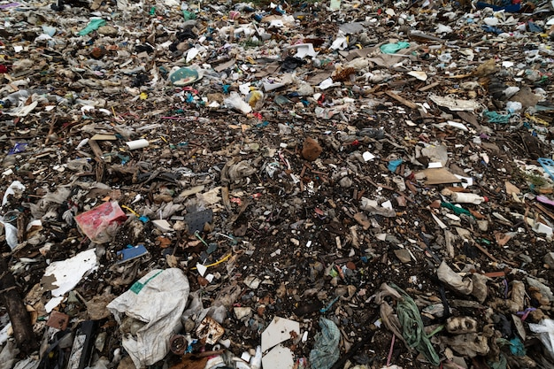 Dirty ground and filled with debris caused by the dumping from factories or industries and houses.