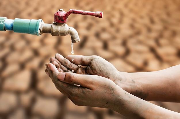 背景に乾燥したひびの入った大地と蛇口から水滴を水滴を待っている汚れた手