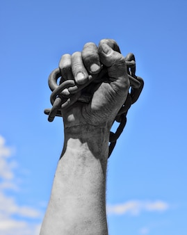 Dirty hand with chain against the blue sky
