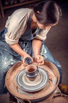 Грязные руки в глине и гончарный круг с изделием