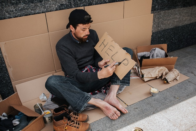 Dirty homeless man is sitting on cardboard and writing down the word help on a piece of paper