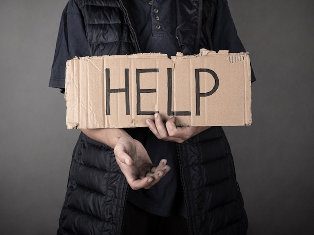 A dirty homeless man stands with a cardboard sign and asks for help.