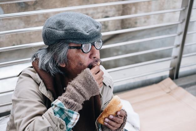 Грязный бездомный сидит и ест хлеб на мосту