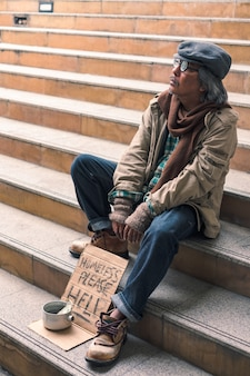 Dirty homeless person sit and looking on stairs with dollar cash in can