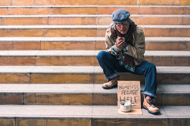 Dirty homeless person sitting on stairs with dollar cash in can, cold and lonely
