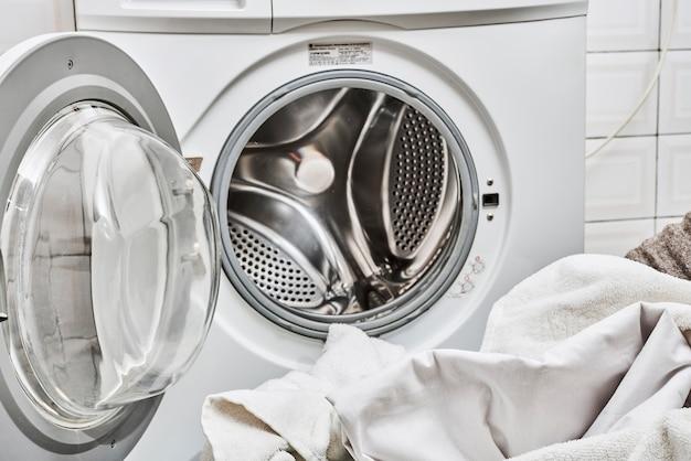 Грязное белье в стиральной машине с открытой дверцей