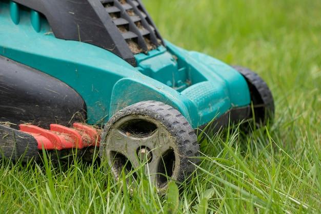 Грязная газонокосилка стоит в стеблях зеленой травы