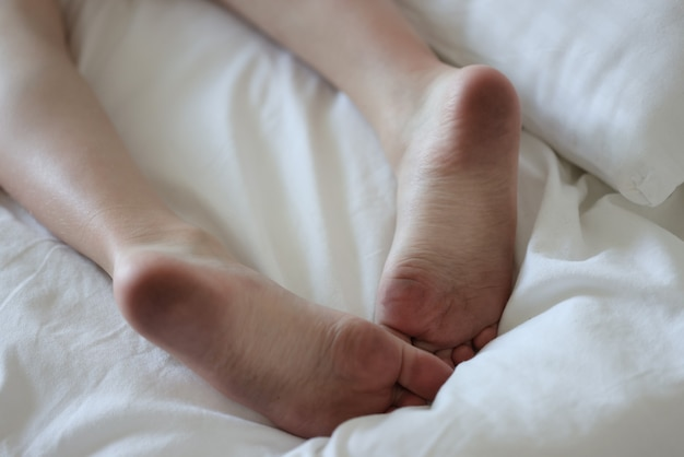 Dirty male feet lie on clean white bed