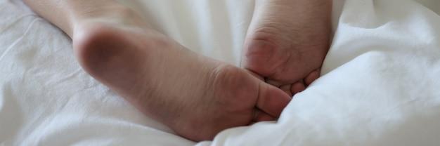 汚れた男性の足はきれいな白いベッドに横たわっています
