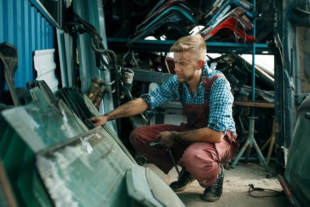 Dirty male repairman choosing glass on car junkyard.