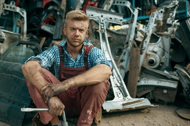 자동차 폐 차장에 렌치로 더러운 남성 수리공. 자동 스크랩, 차량 쓰레기, 자동차 쓰레기, 버려진, 손상 및 부서진 운송