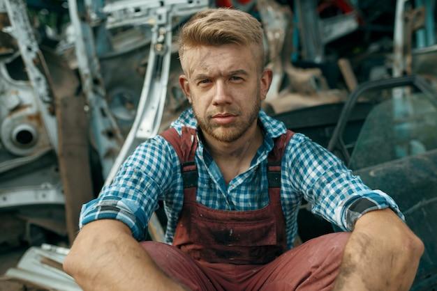 Грязный мужчина-ремонтник с гаечным ключом на свалке автомобилей