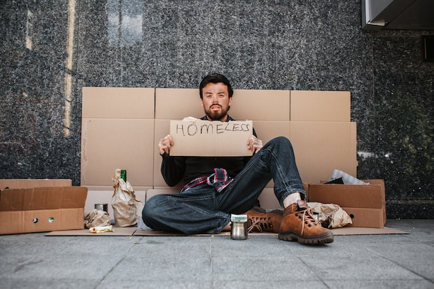 Dirty man sitting on cardboard and looking straight