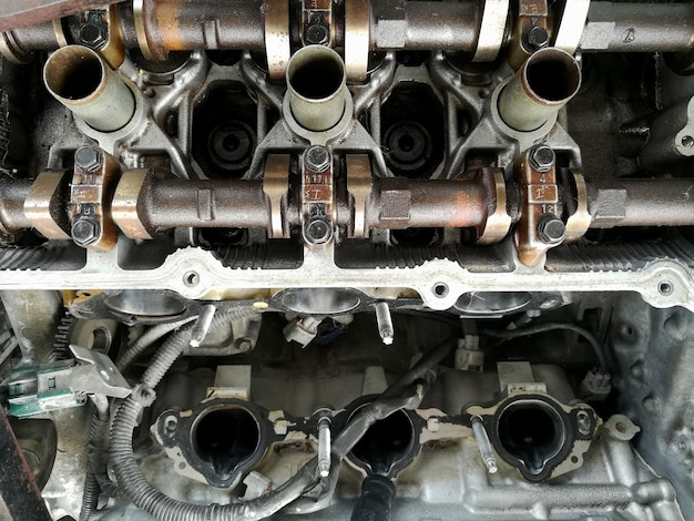 車のサービスセンターでレンチの作業と車のエンジンの修理を行う汚れた整備士