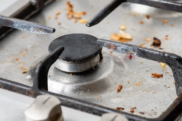 Dirty modern gas stove with a cast-iron grill