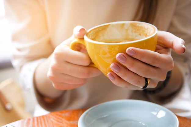 A dirty mug in the hands of a young woman. coffee break, breakfast.