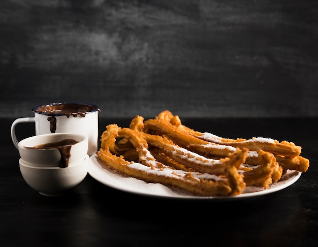 Dirty mugs with melted chocolate and churros