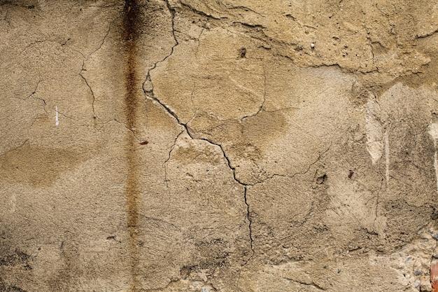 デザインのための汚れた古いひびの入った古い壁のテクスチャ