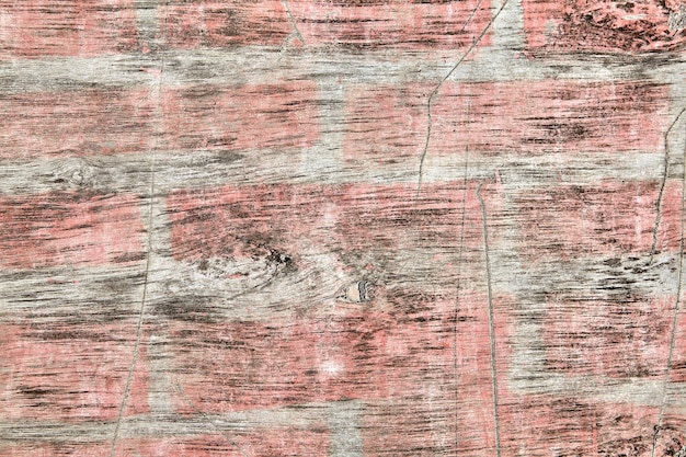 Dirty, old plywood sheet with spots of faded pink paint, scratched and worn, textured surface for backdrop.