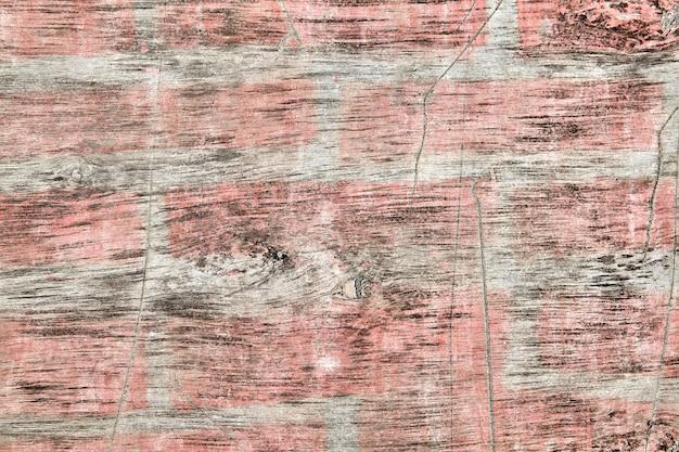 汚れた古い合板のシートで、色あせたピンクのペンキの斑点があり、背景に傷や摩耗があり、テクスチャーのある表面があります。