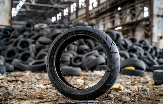 Грязная старая шина стоит на земле рядом с другими использованными шинами на поврежденном заводе. резиновый мусор из машины. крупный план